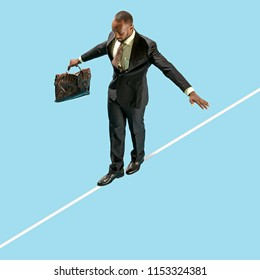 Business man on tightrope concentrate to walking isolated on blue background. Business processes, career, risk concepts
