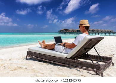 Business man on vacation sits on a tropical beach with his laptop and works