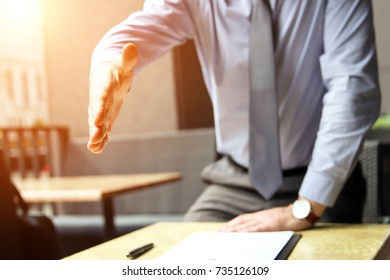 A business man with an open hand extended to handshake