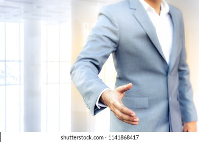 Business man with an open hand ready to seal a deal, partner, copy space. sunlight effect. Wndow interior and business background.