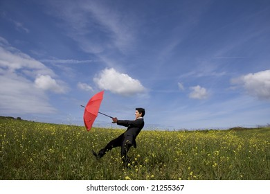 Business man with an open umbrella on the field