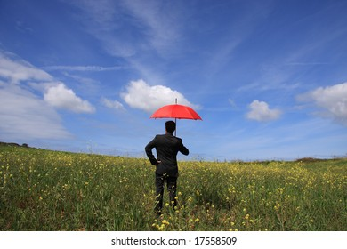Business man with an open umbrella symbolizing protection on the field