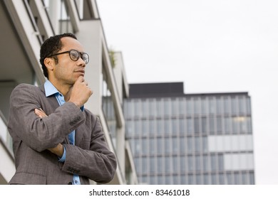 Business man outside office thinking about a good deal