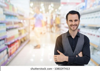 business man, the owner of the convenience store, smiles patiently, welcomes customers to buy in the shop.