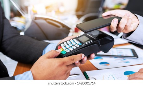 Business man payment by NFC technology with credit card reader machine and smartphone app, asian people.