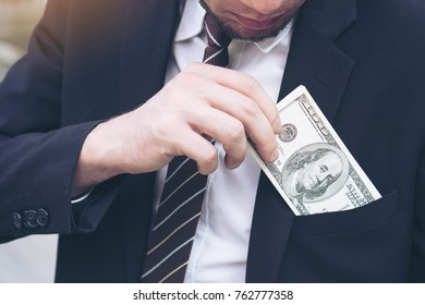 business man Picking up money US dollar bills in  his pocket , concept  business