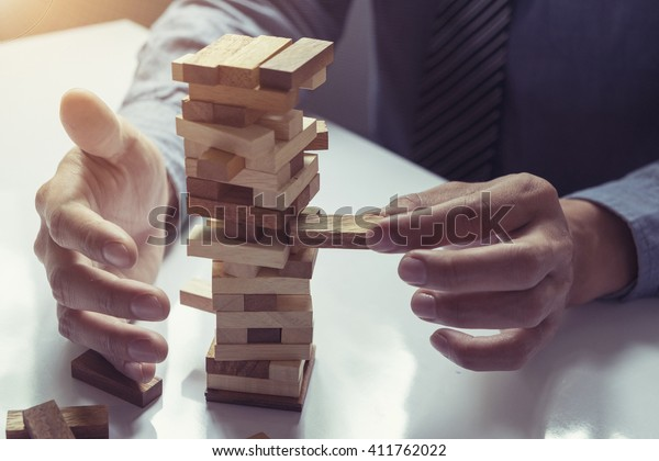 business man placing wooden block on a tower concept risk control, Planning and strategy in business.vintage tone