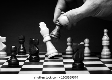Business man playing chess - checkmate. Close-up chess pieces