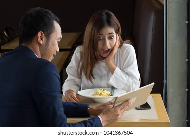 Business man point to tablet with exciting women on the lunch table.