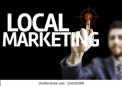 Business man pointing to black board with text: Local Marketing