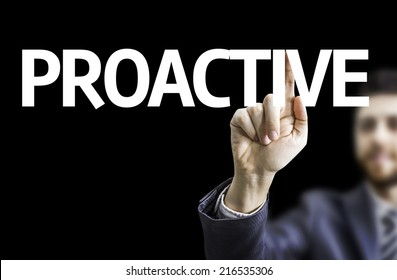 Business man pointing to black board with text: Proactive