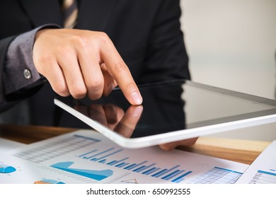 Business man pointing  to digital tablet computer with financial graph in the conference.Business meeting time working with new startup project.presentation concept, Accounting analyze plans.