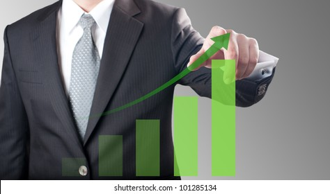 Business man pointing at green bar chart for business growth concept