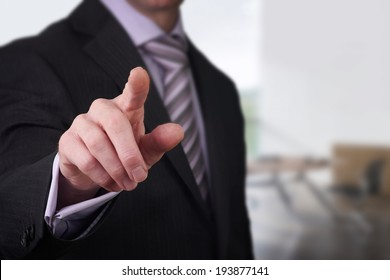 A business man pointing his finger at you.