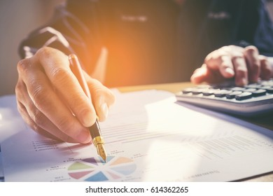 business man pointing his ideas Data and writing business plan at workplace,man holding pens and making notes in documents, on the table