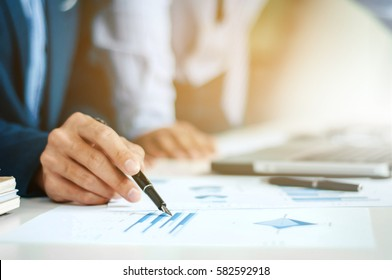 business man pointing on data paper at meeting selected focus on pen