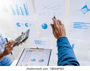 business man pointing on graph paper on the wall