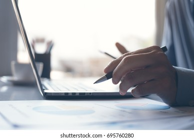 Business man pointing with a pen and working on laptop computer business data,  analysis, information review, business strategy analysis concept, modern technology in smart business