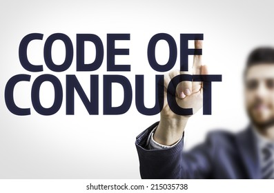 Business man pointing to transparent board with text: Code Of Conduct