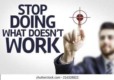 Business man pointing to transparent board with text: Stop Doing What Doesn't Work