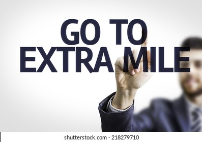 Business man pointing to transparent board with text: Go To Extra Mile