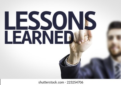 Business man pointing to transparent board with text: Lessons Learned