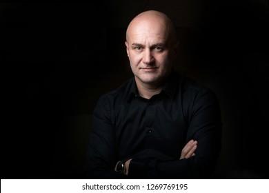 Business man posing in low key in a photo studio