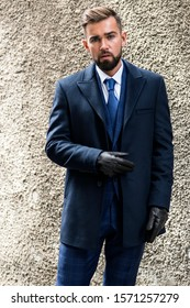 Business man posing in a suit with a tie and in a coat with leather gloves