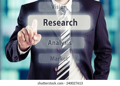Business man pressing research button at his office. Research concept, toned photo.