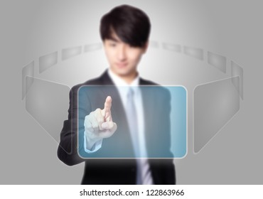 Business man pressing a touch screen button with empty copy space on gray background, asian model