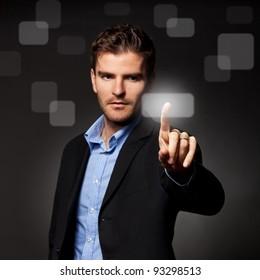 business man pressing a touchscreen button on dark background