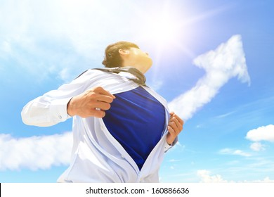 Business man pulling his t-shirt open, showing copy space with a superhero suit , sky and arrow cloud background