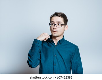 Business man pulls back shirt collar, isolated on gray background