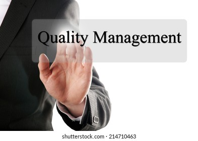 business man push the quality management button on a touch screen