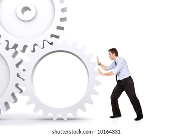 business man pushing a cogwheel to make it work