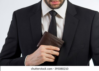 Business man put his leather wallet into his jacket pocket