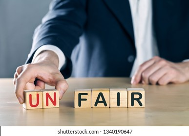 Business man puts away first two letters from the word unfair, so it becomes fair; sports or business fair play concept, blue toned with ligth flare
