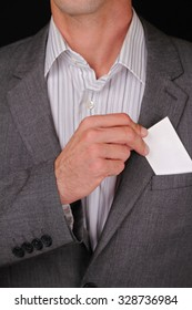 Business man putting a blank business card in his suit pocket. Closeup of a businessman taking a business card from the breast pocket of his suit jacket.
