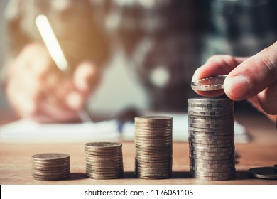 Business man putting coin in glass bottle saving bank and account for his money all in finance accounting concept.