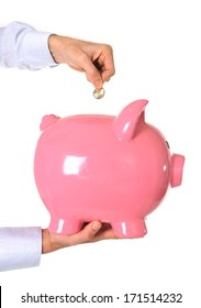 Business Man putting a coin into a huge pink piggy bank isolated on white background