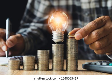 Business man putting coin with light bulb on table for saving bank and account for his money all in finance accounting concept.