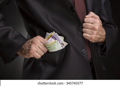Business man putting money into his pocket on dark background