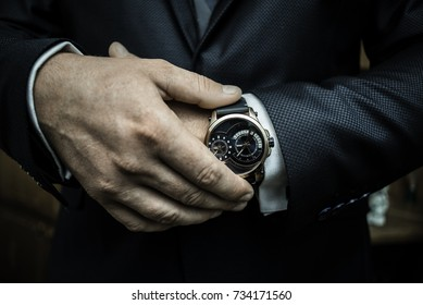 A business man putting on luxury watch and checking time