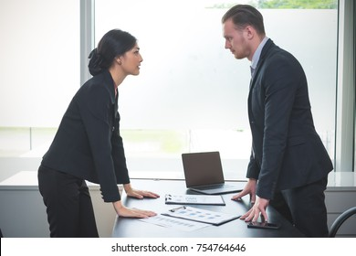 Business man quarrel staring at each other with hostile expressions in the office.