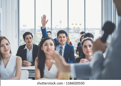 Business man raising hand for asking speaker for question and answer concept in meeting room for seminar