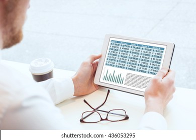business man reading financial report on tablet