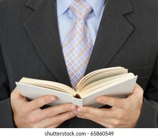 Business man reading a statute book - close-up