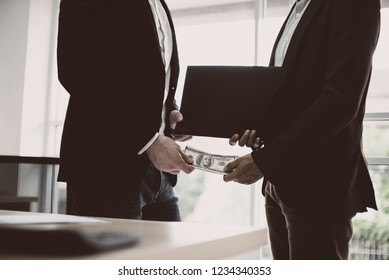 Business man receiving money to take the bribe,Deal business with a handshake and receiving a bribe money,concept of corruption and anti bribery