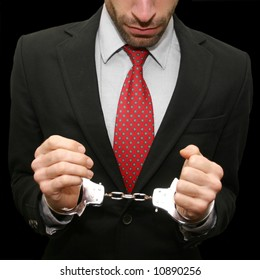 business man with red necktie and black suit in handcuffs isolated on black