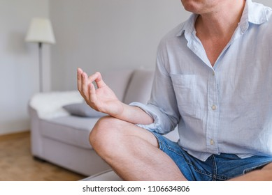 Business man relaxing in the lotus position. Close up. Businessman meditating. Young man in meditation. Mature man meditating alone at home. Freedom and calmness concept